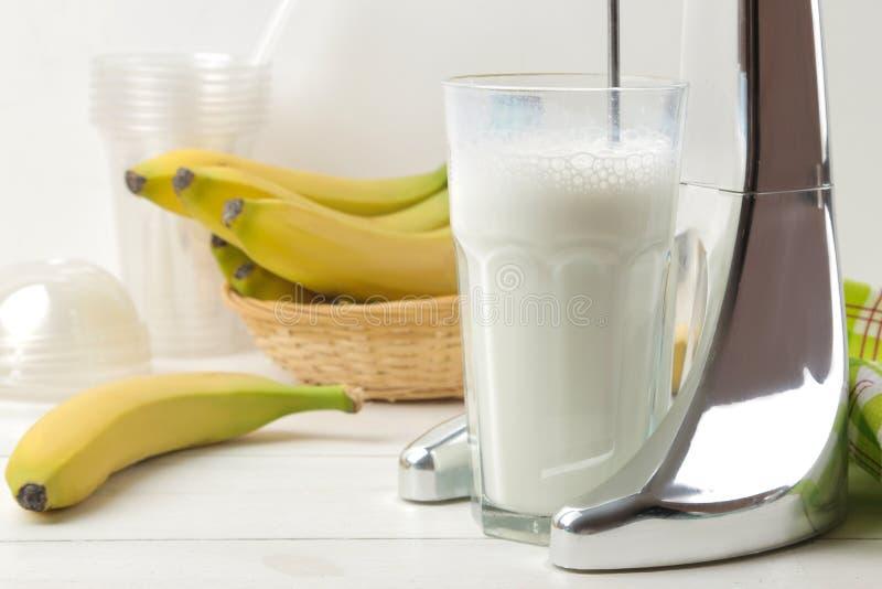 Het maken van een milkshake Mixer voor milkshake en bananen op een lichte achtergrond banaanmilkshake stock afbeeldingen