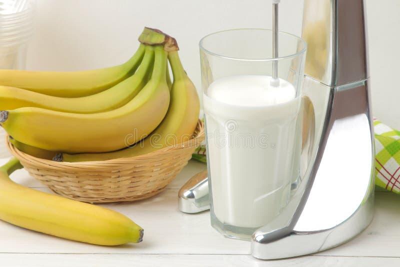 Het maken van een milkshake Mixer voor milkshake en bananen op een lichte achtergrond banaanmilkshake royalty-vrije stock afbeeldingen