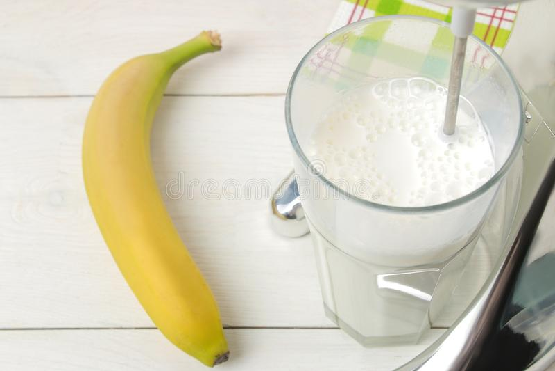 Het maken van een milkshake Mixer voor milkshake en bananen op een lichte achtergrond Close-up stock foto's
