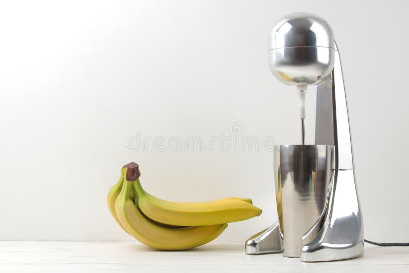 Het maken van een milkshake Mixer voor milkshake en bananen op een lichte achtergrond Vrije ruimte stock fotografie