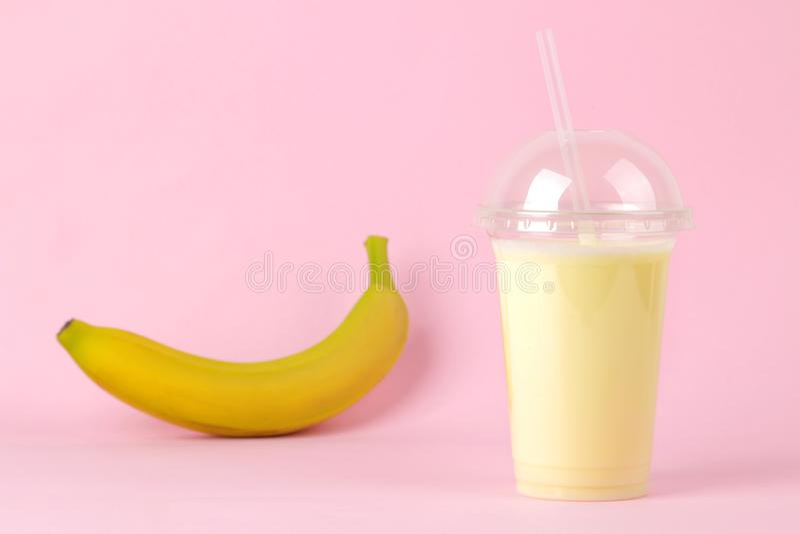 Het maken van een milkshake een plastic beschikbaar glas met een banaanmilkshake en een verse banaan op een heldere in roze achte stock fotografie