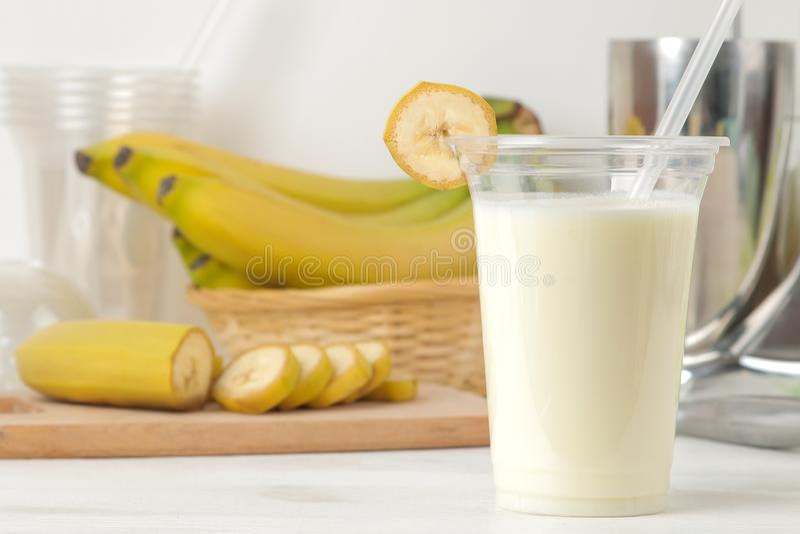 Het maken van een milkshake plastic beschikbaar glas met een banaanmilkshake, ingrediënten voor het koken en mixer op een lichte  royalty-vrije stock foto