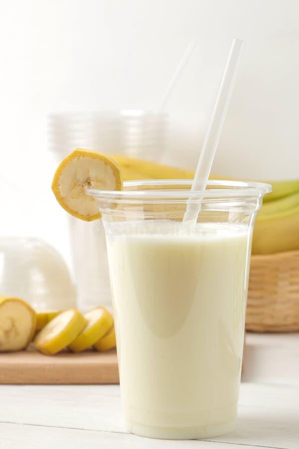 Het maken van een milkshake plastic beschikbaar glas met een banaanmilkshake, ingrediënten voor het koken en mixer op een lichte  stock foto