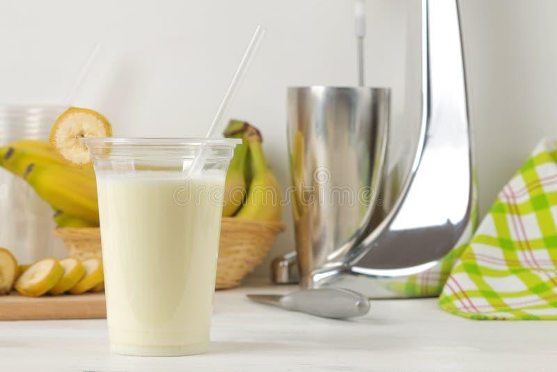 Het maken van een milkshake plastic beschikbaar glas met een banaanmilkshake, ingrediënten voor het koken en mixer op een lichte  stock fotografie
