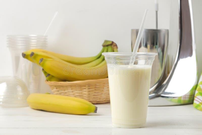 Het maken van een milkshake plastic beschikbaar glas met een banaanmilkshake, ingrediënten voor het koken en mixer op een lichte  stock foto's