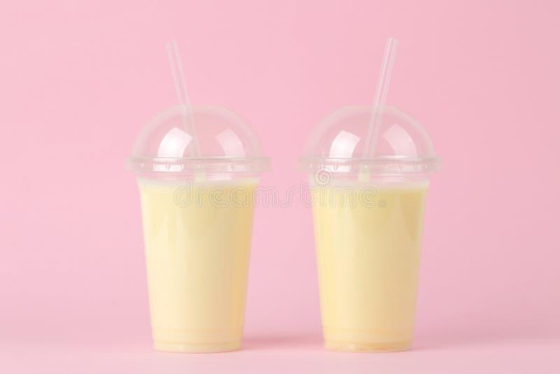 Het maken van een milkshake plastic beschikbaar glas met een banaanmilkshake op een heldere in roze achtergrond stock afbeelding