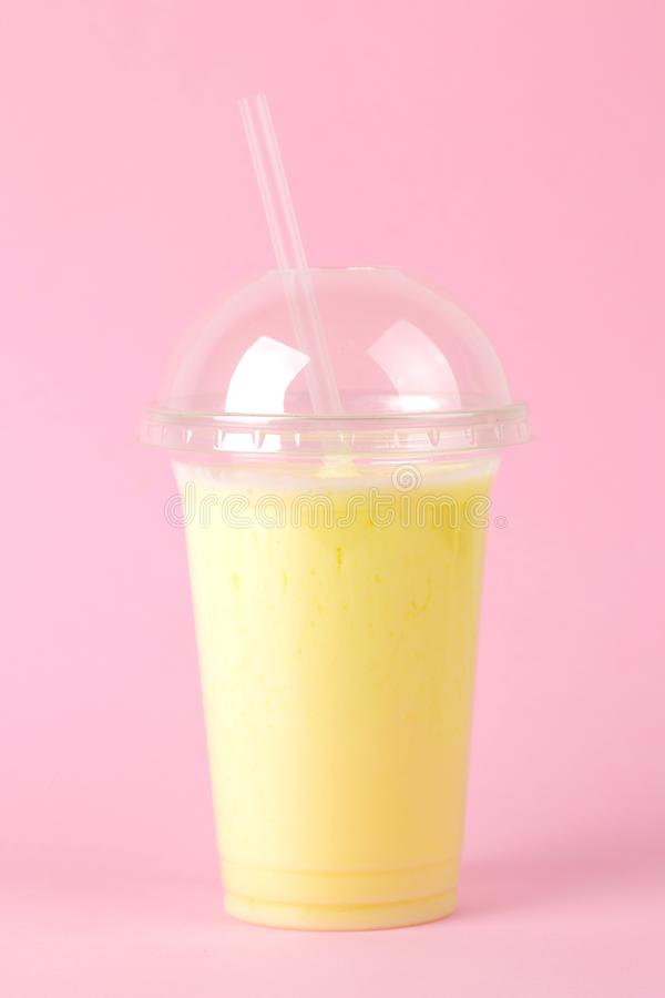 Het maken van een milkshake plastic beschikbaar glas met een banaanmilkshake op een heldere in roze achtergrond royalty-vrije stock foto