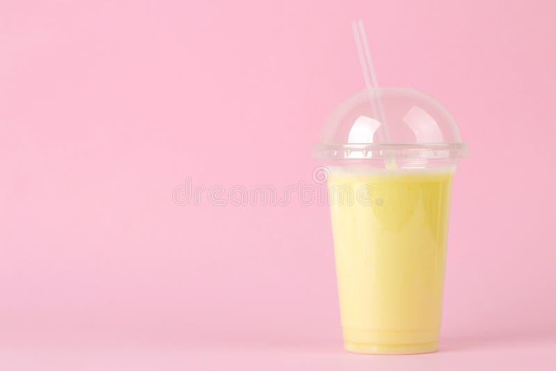 Het maken van een milkshake plastic beschikbaar glas met een banaanmilkshake op een heldere in roze achtergrond Ruimte voor tekst royalty-vrije stock fotografie