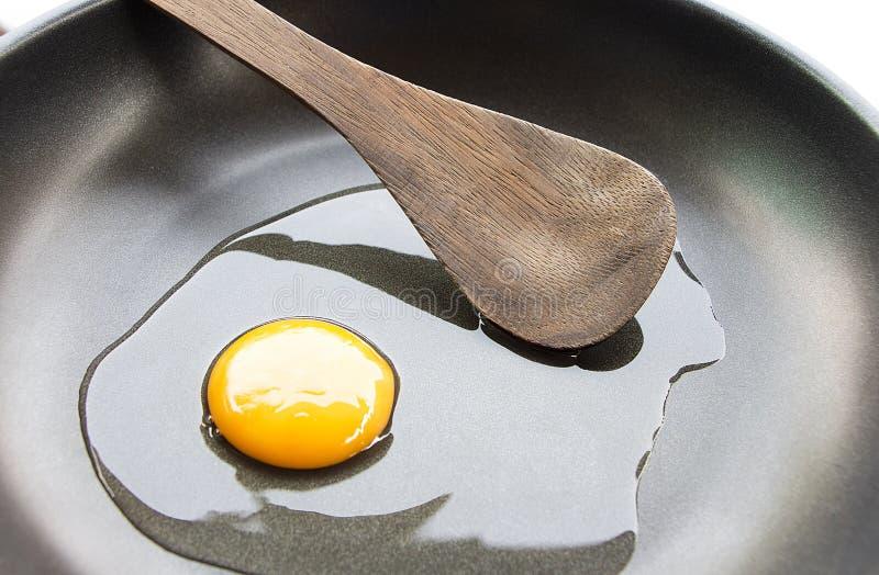 Het maken van eieren in een steelpan en een houten gietlepel stock foto's