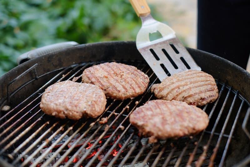 Het maken van eigengemaakte burgers bij de grill stock afbeelding