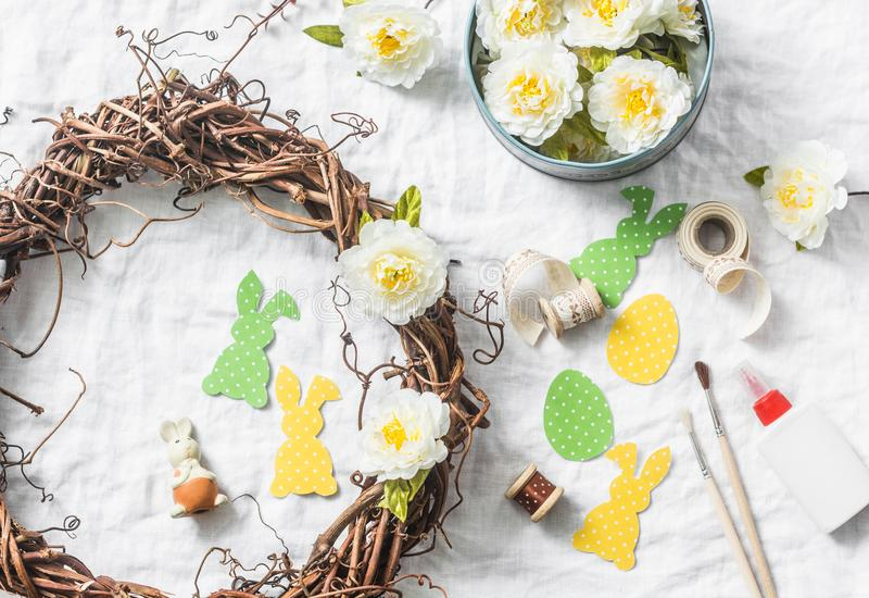 Het maken van eigengemaakte Pasen-kroon van wijnstokken met bloemen, document konijnen, linten op een witte achtergrond, hoogste  royalty-vrije stock foto