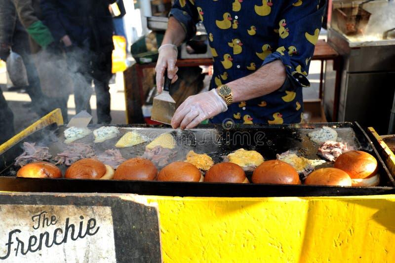 Het maken van Franse hamburgers bij Broadway-markt, Londen royalty-vrije stock afbeeldingen