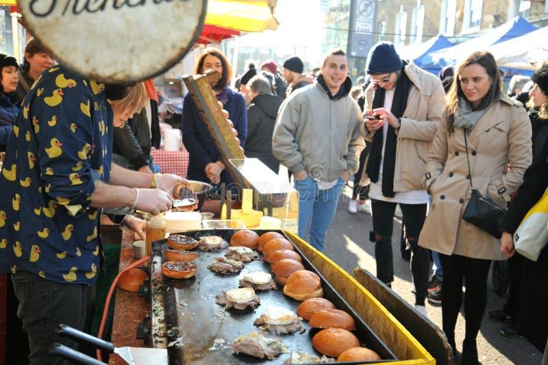 Het maken van Franse hamburgers bij Broadway-markt, Londen stock afbeeldingen