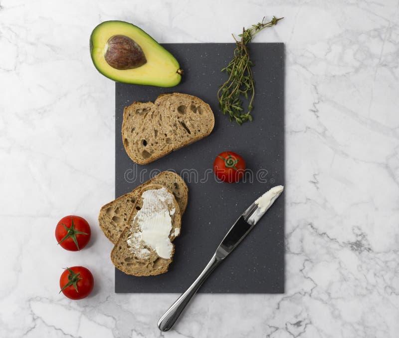 Het maken van gezonde sandwiches met roomkaasavocado, tomaten en thyme stock afbeelding