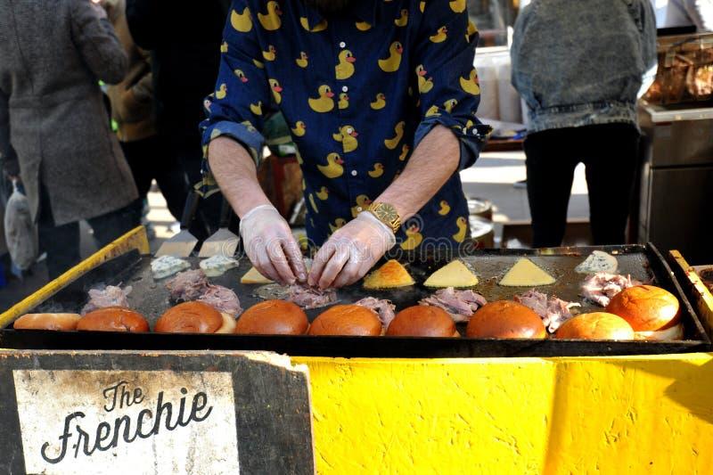 Het maken van hamburgers bij Broadway-markt, Londen stock afbeeldingen
