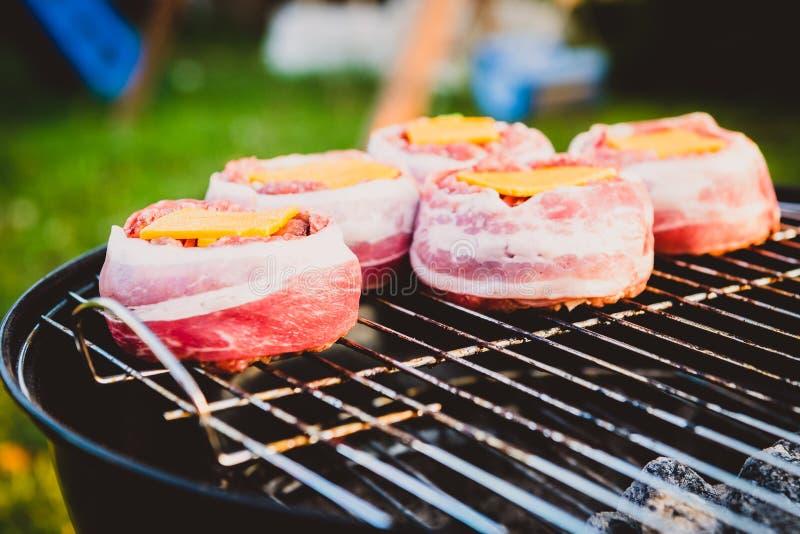 Het maken van naar huis gemaakt Bier kan Bacon Burgers bij de barbecuegrill stock afbeeldingen