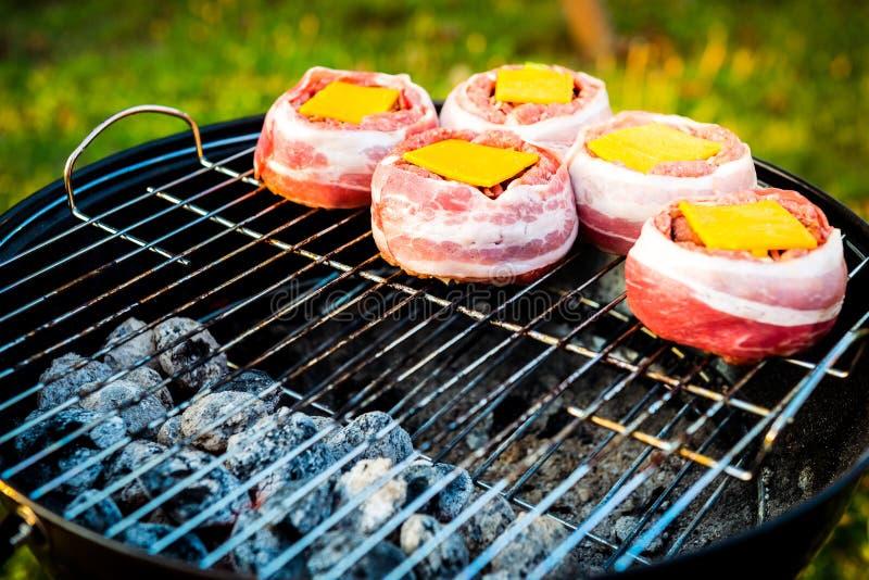 Het maken van naar huis gemaakt Bier kan Bacon Burgers bij de barbecuegrill royalty-vrije stock foto