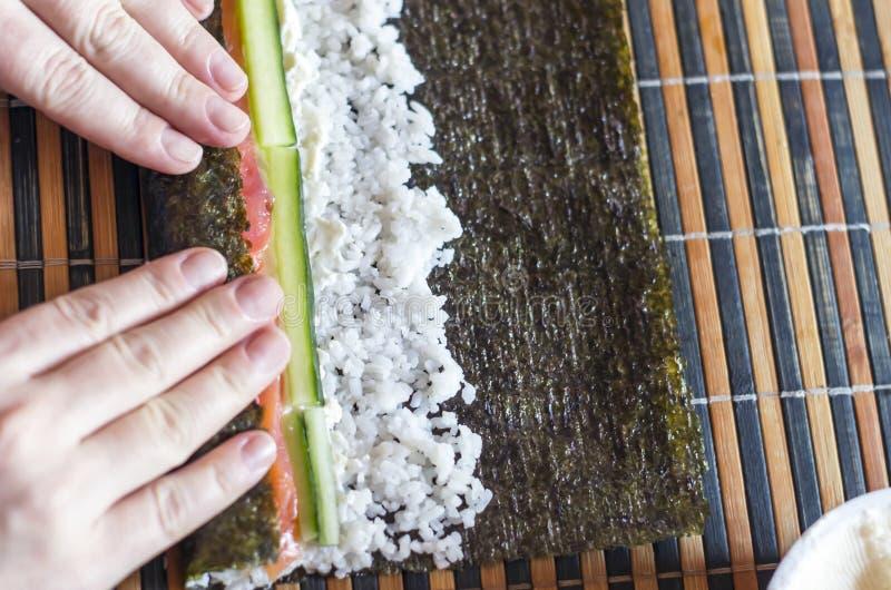 Het maken van Sushi rolt thuis: Vrouwelijk Handenbroodje Nori Seaweed Sheet op een Bamboemat Ingrediënten: Salmon Fish Strips, Ko stock afbeeldingen