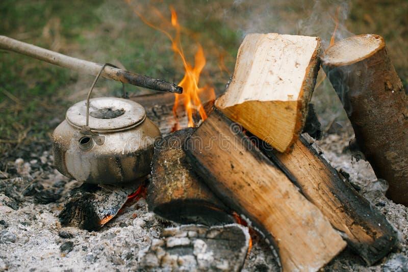 Het maken van thee of koffie in het kampvuur op aard royalty-vrije stock afbeeldingen