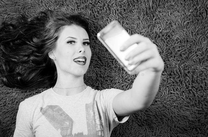 Het maken van zelfbeeld bij het mobiele telefoon jonge mooie vrouw ontspannen op tapijtachtergrond Zwart-wit beeld royalty-vrije stock foto