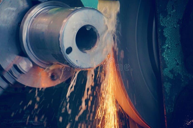 Het malen van metaal, definitieve verwerking van een deel op een precisie malende machine met vonken en het koelen stock foto