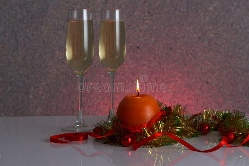 Het malplaatje van de groetkaart van gouden en groen klatergoud met rode Kerstmisballen, rood lint, oranje kaars en twee glazen v royalty-vrije stock fotografie