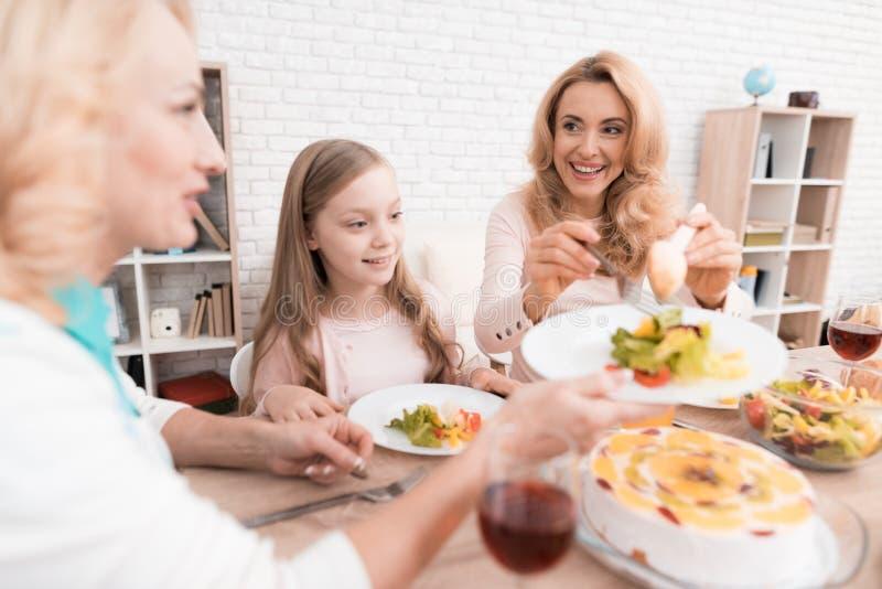 Het mamma, de grootmoeder en het meisje dineren samen thuis stock afbeelding