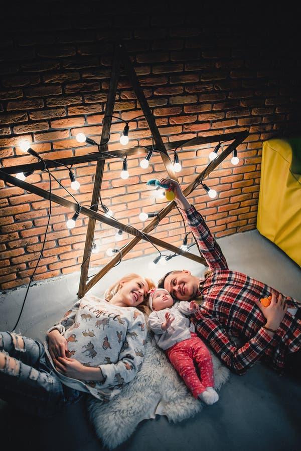 het mamma, de papa en de baby liggen op een wollen tapijt en een glimlach royalty-vrije stock foto