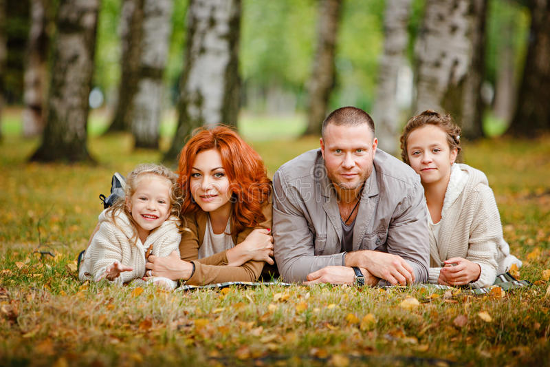 Het mamma, de papa en twee charmante zusters in hetzelfde krullende beige breien s stock fotografie