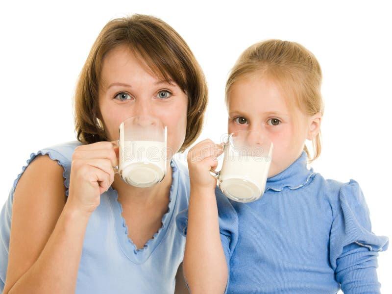 Het mamma en de dochter drinken melk. stock afbeelding