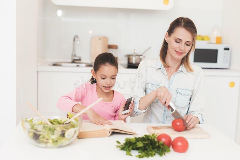 Het mamma en de dochter hebben pret terwijl het voorbereiden van een salade Zij zijn in een heldere keuken royalty-vrije stock afbeelding