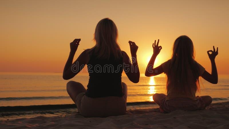 Het mamma en de dochter mediteren door het overzees bij zonsondergang Gezondheid en gelukkige tijd samen stock afbeeldingen