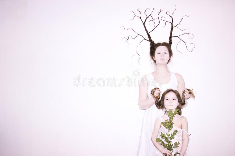Het mamma en de dochter in witte kleding op een witte achtergrond schilderen de winter af en springen op, houdend bloemen en een  royalty-vrije stock fotografie