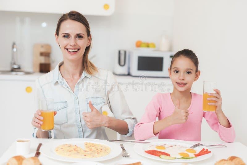 Het mamma en de dochter zitten in de keuken en hebben ontbijt zij pret bij ontbijt hebben stock afbeelding