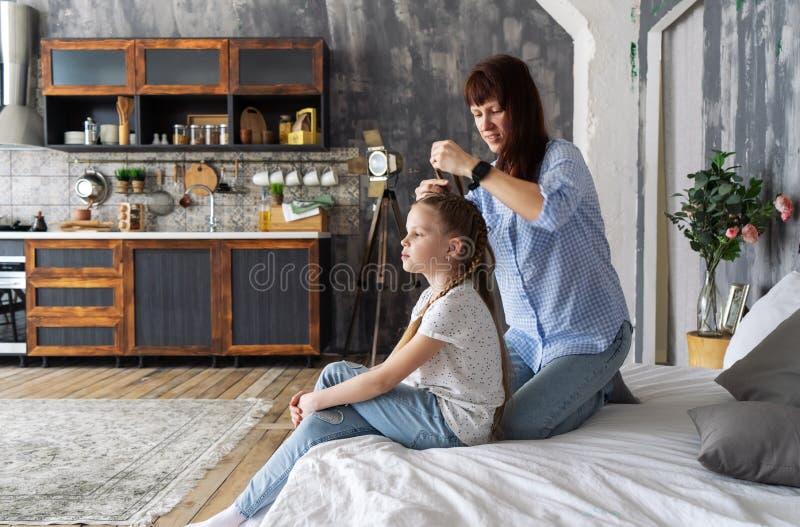 Het mamma en de dochter zitten op het bed en het mamma vlecht zacht vlechten Europees Binnenland stock afbeelding