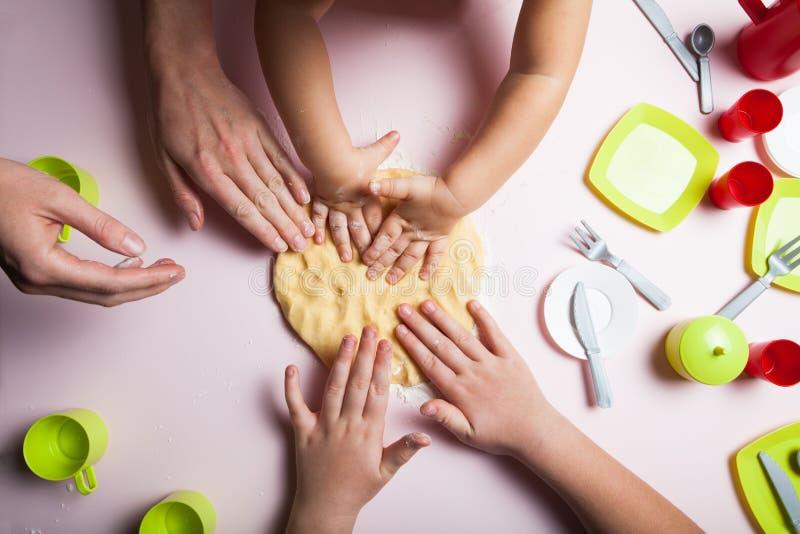 Het mamma en de kinderen bakken koekjes in de keuken en verfraaien koekjes op Kerstavond, de hoogste mening stock fotografie