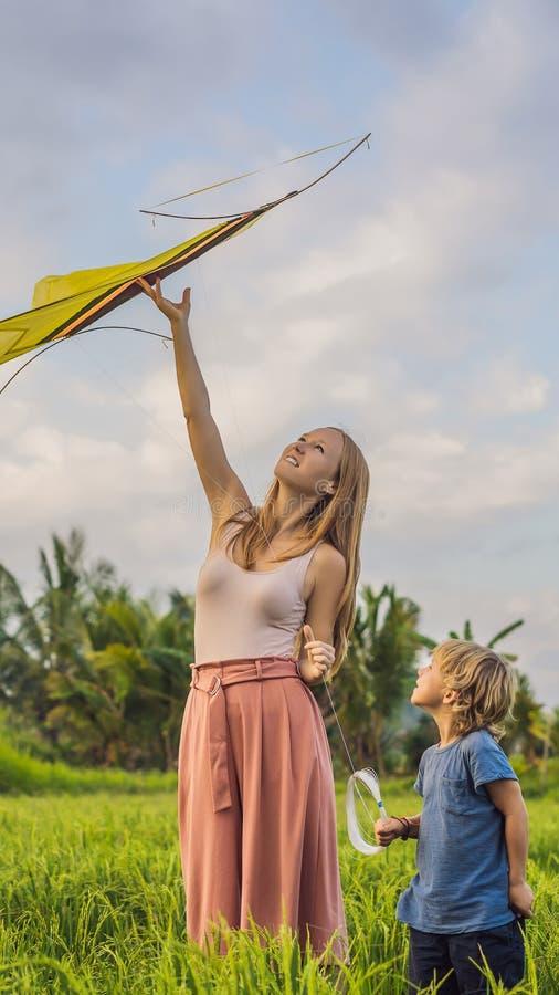 Het mamma en de zoon lanceren een vlieger in een padieveld in Ubud, het Eiland van Bali, het VERTICALE FORMAAT van Indonesië voor royalty-vrije stock foto