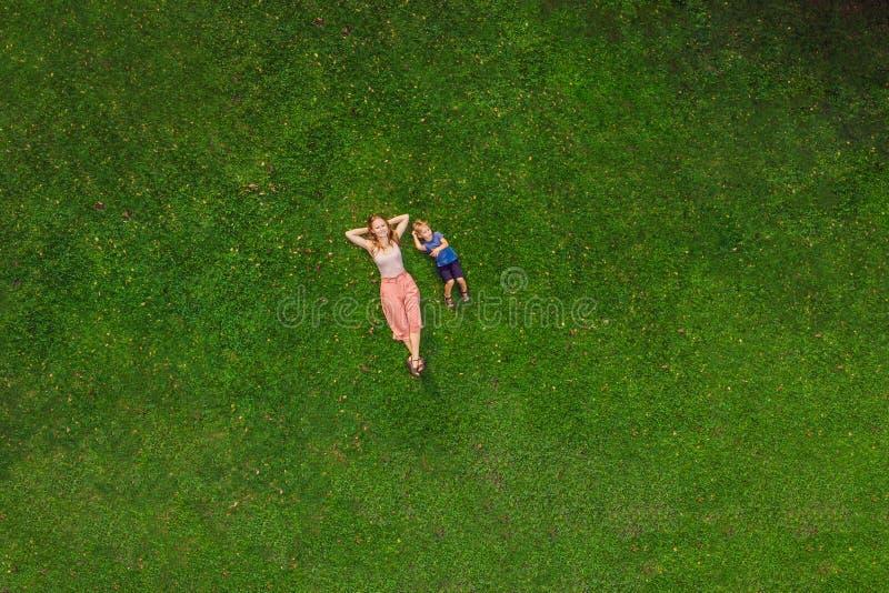 Het mamma en de zoon liggen op het gras in het park, foto's van de hommel, quadracopter royalty-vrije stock fotografie