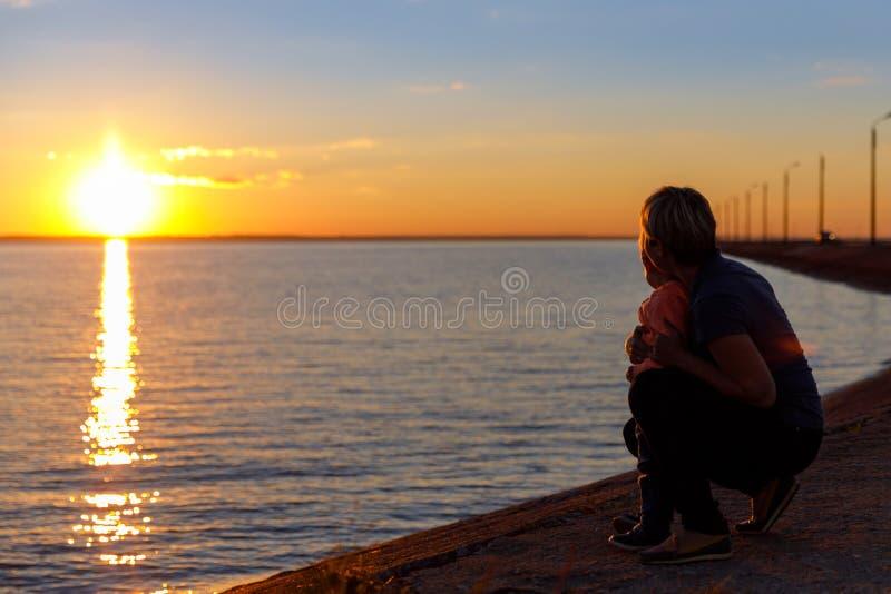 Het mamma en de zoon op de rivierbank van Volga bij zonsondergang, silhouetteren een familie in de avond in de zomer bij zonsonde royalty-vrije stock afbeelding