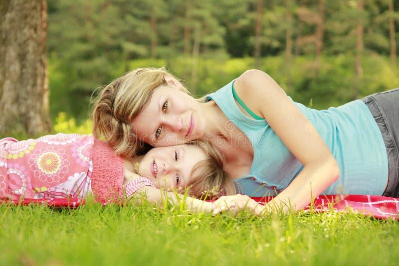 Het mamma en haar weinig dochter liggen op het gras stock afbeeldingen