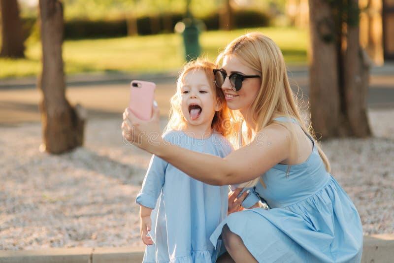 Het mamma en haar weinig dochter maken selfie in het park stock fotografie
