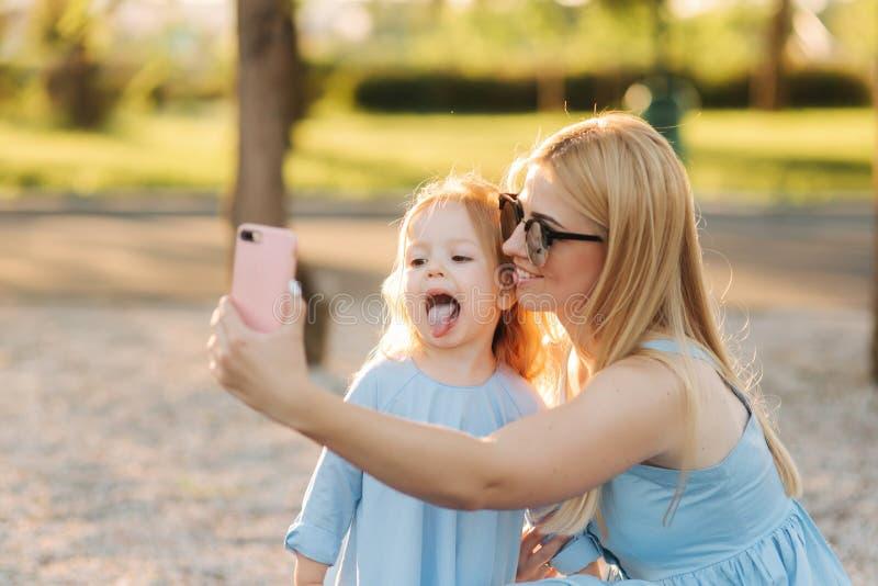 Het mamma en haar weinig dochter maken selfie in het park royalty-vrije stock foto