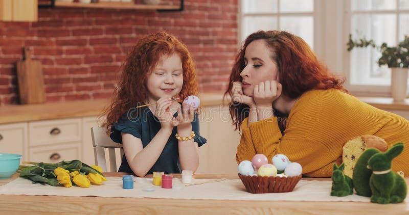 Het mamma en haar weinig dochter treffen voor Pasen voorbereidingen Meisje die paaseieren in comfortabele keuken schilderen Gliml stock afbeelding