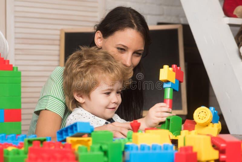 Het mamma en het kind bouwen uit kleurrijke plastic blokken stock foto's