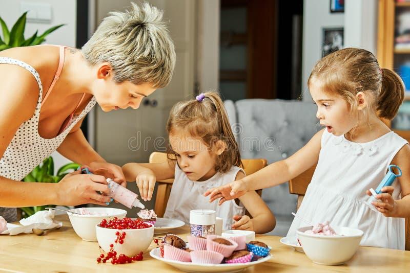 Het mamma en twee mooie dochters verfraaien en eten cupcakes stock fotografie
