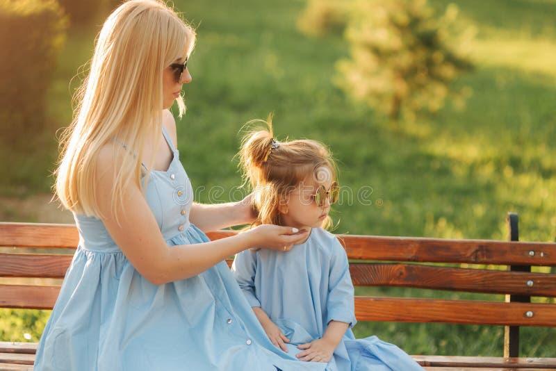 Het mamma en zijn kleine dochter zitten op een bank in het park royalty-vrije stock foto