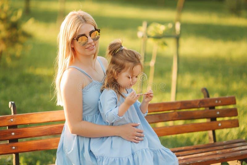 Het mamma en zijn kleine dochter zitten op een bank in het park stock fotografie