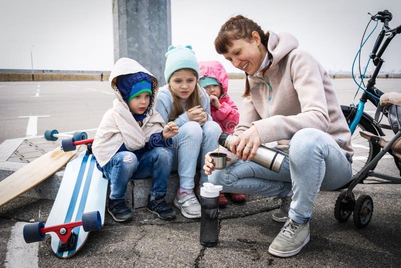 Het mamma giet hete thee van een thermosfles voor drie kinderen De jonge geitjes schaatsten op een vleetraad en bevroren stock afbeelding