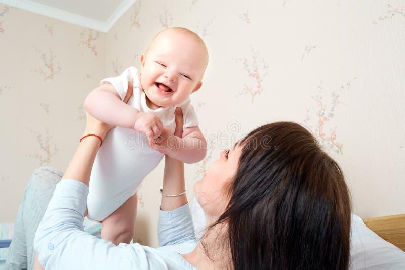 Het mamma hief haar handen op baby, baby het glimlachen en het lachen op Gelukkig stock afbeeldingen