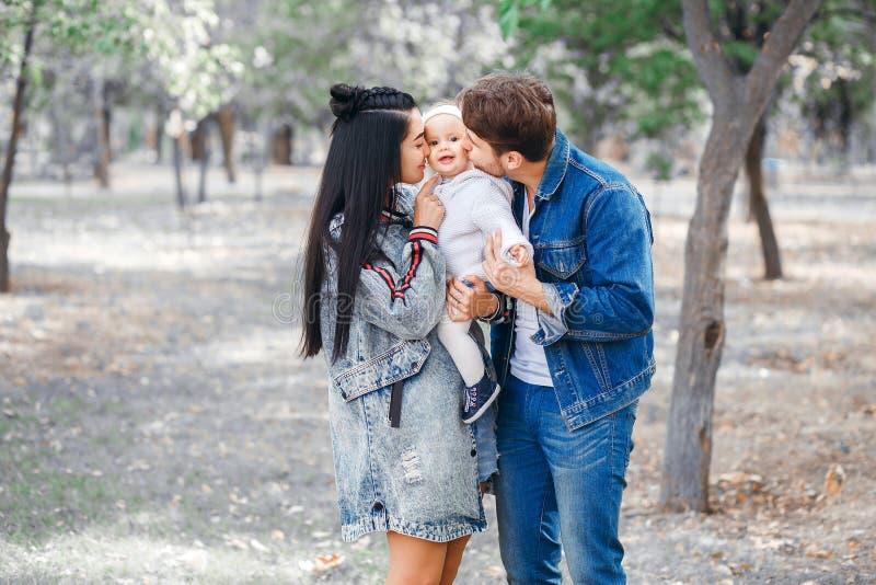 Het mamma houdt een klein kind in haar wapens, dichtbij papa, familie voor een gang in het park royalty-vrije stock afbeeldingen